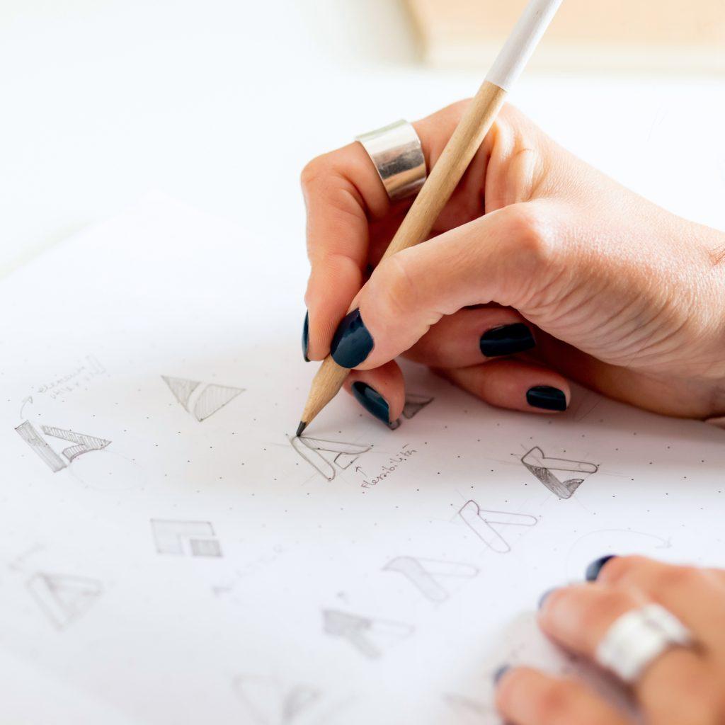 mano di un grafico donna che disegna un logo